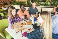Firma wielokulturowi m?odzi ludzie w cukiernianej ?asowanie pizzy, pij?cy koktajl, mie? zabaw? zdjęcie royalty free