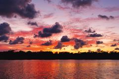 Crimson and charcoal colored cumulus cloud, sunset seascape. The Firmament housing a brilliant atmospheric cloudy crimson red sky sunset display over water and royalty free stock images