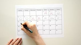 Firme el día en el calendario con una pluma, dibuje una sonrisa almacen de metraje de vídeo