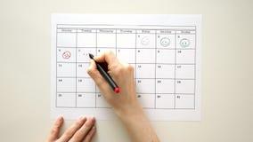 Firme el día en el calendario con una pluma, dibuje una sonrisa metrajes