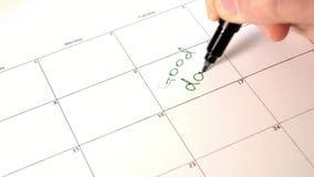 Firme el día en el calendario con una pluma, dibuje un buen mún día metrajes