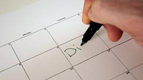 Firme el día en el calendario con una pluma, dibuje un buen mún día