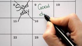 Firme el día en el calendario con una pluma, dibuje un día triste