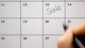 Firme el día en el calendario con una pluma, dibuje una venta