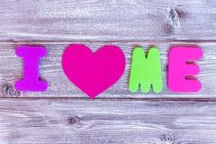 Firme i me aman hizo de letras coloridas y de un corazón en el fondo de madera, concepto cariñoso del uno mismo imagen de archivo libre de regalías