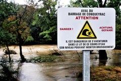 Firme la advertencia del peligro del agua de la presa contra la corriente caído Imagen de archivo