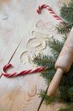 Firme la Feliz Año Nuevo 2018 en la harina en la tabla de madera adornada con los caramelos rojos, la Navidad tres ramas y el rod Imágenes de archivo libres de regalías