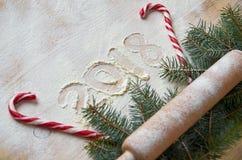 Firme la Feliz Año Nuevo 2018 en la harina en la tabla de madera adornada con los caramelos rojos, la Navidad tres ramas y el rod Foto de archivo