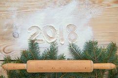 Firme la Feliz Año Nuevo 2018 en la harina en la tabla de madera adornada con la Navidad tres ramas y rodillo de madera Fotos de archivo libres de regalías