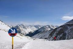 Firme la pendiente en las cuestas en las montañas alpinas, la persona va a ir abajo del esquí, muchos picos de montaña a continua Fotografía de archivo
