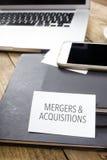 Firme las fusiones y las adquisiciones en la mesa de la oficina con el de electrónico Imagen de archivo libre de regalías