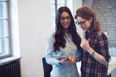 Firmenkundengeschäftfrauen, die im Büro sich beraten lizenzfreies stockfoto