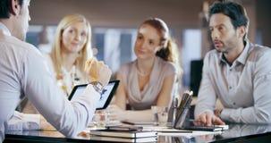 Firmenkundengeschäftteamarbeits-Bürositzung Vier kaukasische Geschäftsmann- und Geschäftsfrauleute gruppieren Unterhaltungsstrate stock video
