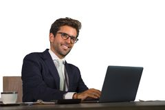 Firmenlokalisiertes Unternehmensporträt des jungen hübschen und attraktiven Geschäftsmannes, der am Bürolaptopcomputertisch läche stockbilder