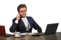 Firmenlokalisiertes Unternehmensporträt des jungen hübschen und attraktiven Geschäftsmannes, der am Schreibtisch spricht am Handy stockbild