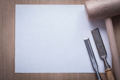 Firmer chisels lump hammer and clean sheet of paper on wooden bo Stock Photography