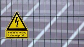 Firmi con l'alta tensione di parole - il pericolo per vita in tedesco davanti ai pannelli solari Fotografie Stock Libere da Diritti