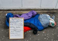 Firmi dal lato del marciapiede del senzatetto con il sacco a pelo, l'alimento e la tazza per cambiamento - concetto di austerità, immagini stock