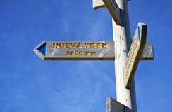 Firmi il segno della distanza fra Pamplona e New York fotografia stock libera da diritti