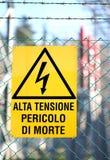 Firmi scritto in italiano che significa il pericolo ad alta tensione della morte Fotografie Stock