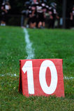 First and 10 yards to go. A 10 yard line marker surrounded by grass.  The white yard line and a football huddle is visible in the blurred background.  The number Royalty Free Stock Photo