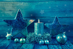 First advent: one burning golden candle on a wooden background. Royalty Free Stock Images