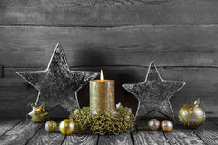 First advent: one golden burning candle on wood for decorations. Stock Photo