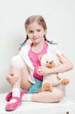 First Aid. Little girl with bandage on knee Royalty Free Stock Images