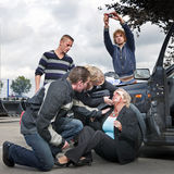 First aid. Bystanders checking up and providing first aid to an injured bleeding driver after a car crash. A man is taking pictures Royalty Free Stock Photos