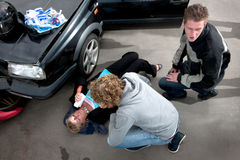 First aid. Bystander providing first aid to an injured woman lying on the ground, bleeding, after a car crash, with a first aid kit on the hood of her damaged Royalty Free Stock Photo