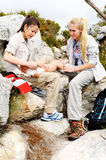 First aid. A women has sprained her ankle while hiking, her friend uses the first aid kit to tend to the injury Royalty Free Stock Image