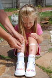 First aid. Wounded little Caucasian white girl receiving first aid from her grandma after playing and having an accident in the garden outdoors. Grandmother is stock images