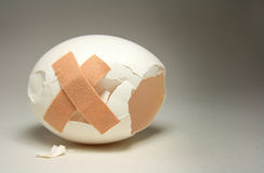 First aid. Cracked egg with two plasters Stock Photography