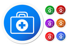 First aid badge. Circular first aid badge with small case and blue cross inside a white circle imprinted on the side. Six small replicas in green, brown, purple Royalty Free Stock Images