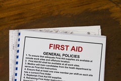 First Aid basic training manual. With blueprints in a wood texture background stock images