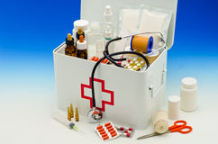 First aid box. Open first aid box filled with medical supplies in blue background Royalty Free Stock Photography
