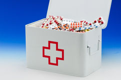 First aid box. Open first aid box filled with pills. Blue background. Drugs abuse Stock Image