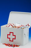 First aid box. Open first aid box filled with pills. Blue background. Drugs abuse Royalty Free Stock Image