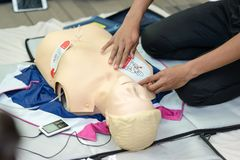First aid cardiopulmonary resuscitation course using AED training. Selective focus placing electrode stock photography