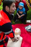 First aid course for children. BRATISLAVA, SLOVAKIA - MAY 18, 2019: Male rescuer demonstrating CPR to kids with an emergency dummy in Bratislava, Slovakia stock images