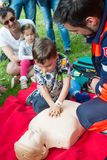 First aid course for children. BRATISLAVA, SLOVAKIA - MAY 18, 2019: Male rescuer demonstrating CPR to kids with an emergency dummy in Bratislava, Slovakia stock photo
