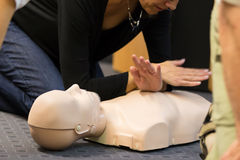 First aid CPR seminar. A group of adult education students practitcing CPR chest compressioon on a dummy Stock Photo