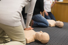 First aid CPR seminar. A group of adult education students practitcing CPR chest compressioon on a dummy Royalty Free Stock Image