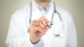 First Aid, Doctor writing on transparent screen Royalty Free Stock Photo