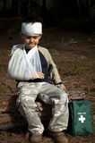 First Aid in the Forest. First Aid treatmant given to a young boy in the forest, showing an arm sling and a head injury Stock Photos