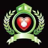 First aid icon in heart in green royal crest Stock Images