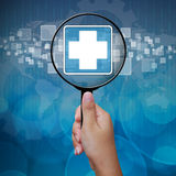 First Aid icon in Magnifying glass Stock Photos