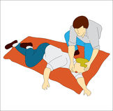 First Aid Instructor. A man gives first aid to another man in need over a red blanket Stock Photos