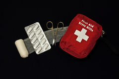 First aid kit. With pills, bandage and scissors on black bacground Stock Photography
