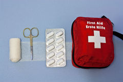 First aid kit. With bandage, scissor and pills on blue textile background Royalty Free Stock Images